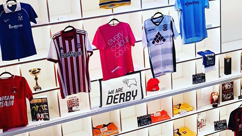 Close up showing magenta Everycolour T-shirt on display with other football shirts and memorabilia