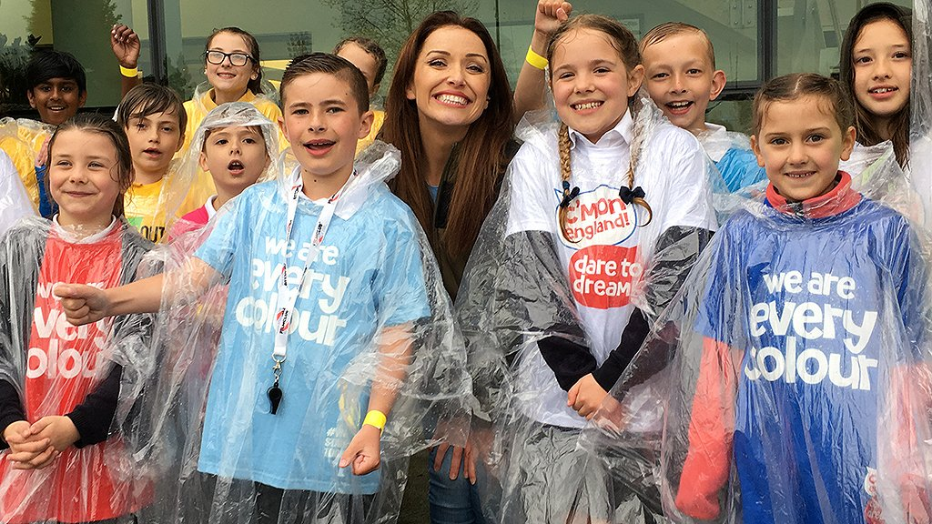 Presenter Natalie smiles as she poses for a photo with members of the choir, who are wearing waterproof ponchos because of the rain