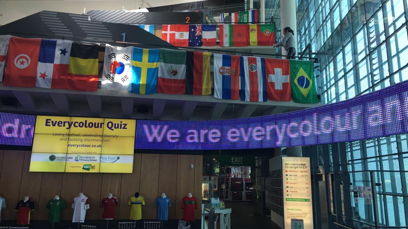 View of the museum atrium with the animated Everycolour slogan on the moving sign with the flags form all the Wolrd Cup nations hanging above.
