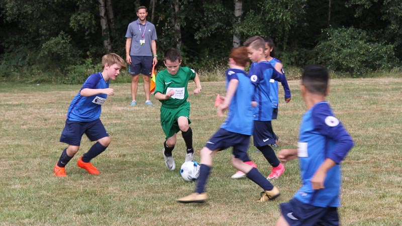 Players from Broad Oak surround a forward from St Wilfrid's CE as he dribbles past them all