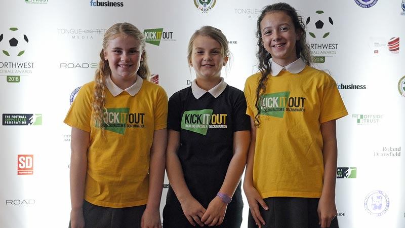 Three girls pose in front of the sponsors board