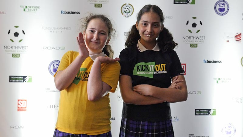 Two girls pose in front of the sponsors board