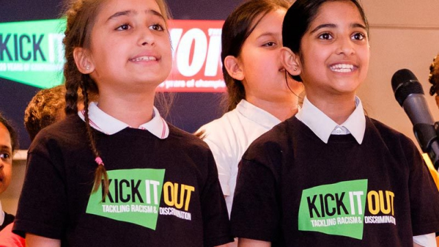 Two girls wearing black Kick It Out T-shirts sing with passion